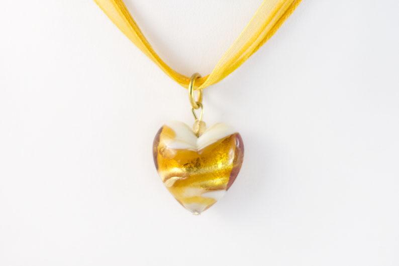 Pendentif en forme de cœur enfermant une feuille d'or 24 carats ou d'argent 925. C'est un bijou entièrement réalisé à la main qui révèle la précision des maîtres verriers de Venise. Idéal pour un cadeau d'amoureux, il restera éternel car le verre ne ternit pas et les couleurs restes éblouissantes.