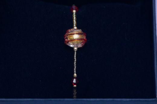 Un bracelet d'une grande finesse réalisé en perles de conteria. Il est surmonté d'une très originale perle en verre de Murano recouverte d'un filigrane en spirale.